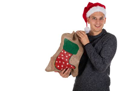 Photo of a young , handsome  man holding colourful christmas  bag
