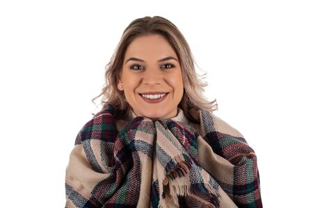 Beautiful young woman wrapped up in a trendy winter scarf is smiling to the camera on isolated Foto de archivo - 135149209