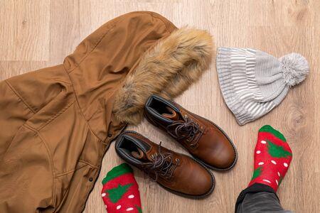 Warm winter clothes, mens boot, coat on wooden floor
