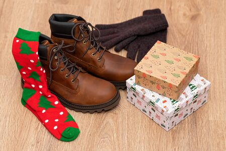 Warm winter clothes, mens boots, gloves and gift box on wooden floor