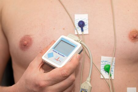 Young man with  heart diseases wearing holter monitor device for an electrocardiogram