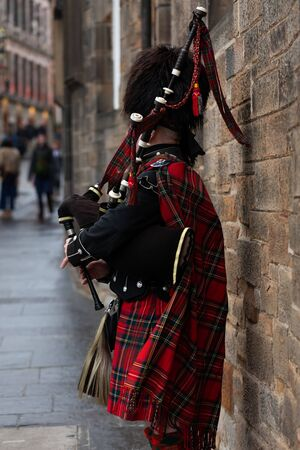 Scottish piper playing the bagpipes in traditional costume in Edinburgh