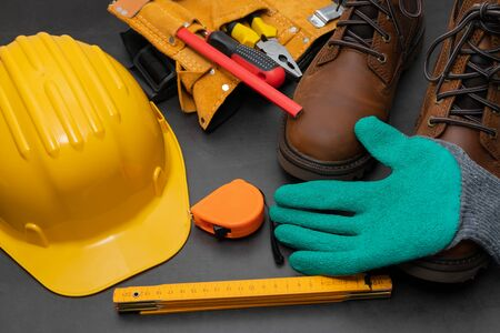 Safety gloves, boots , yellow hard hat on a black background