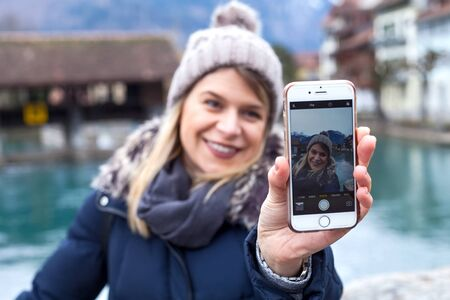 Beautiful young woman taking a selfie in Interlaken, Switzerland - Tourism on wintertime