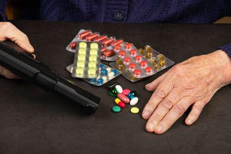 Depressed elderly woman holding a gun in her hands