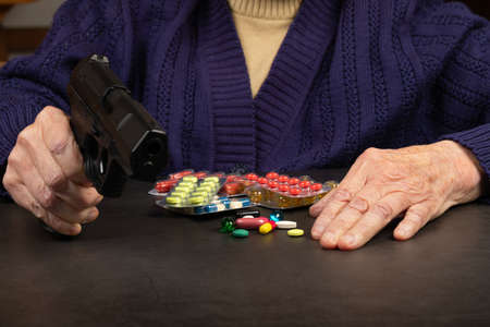 Depressed elderly woman holding a gun in her hands Banque d'images