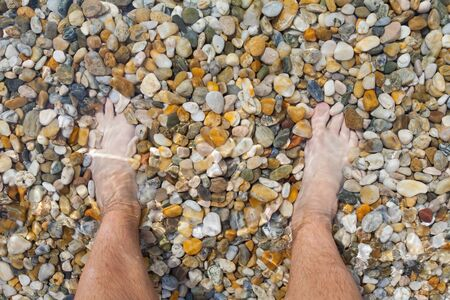 Bare feet at the seaside on summertime, sandy beach
