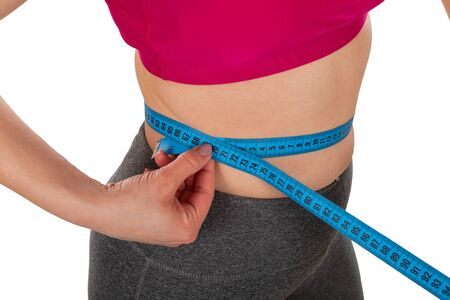Young females waistline, holding a measuring tape on isolated background - weight loss, diet, body shaping concept