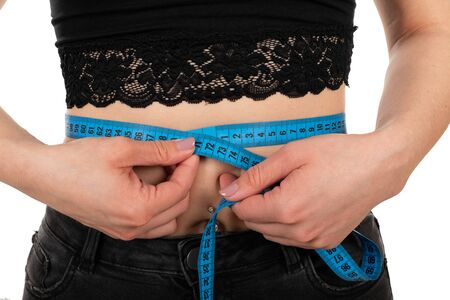 Close up picture of fit young woman's waistline holding a measuring tape, wearing jeans and black lace top