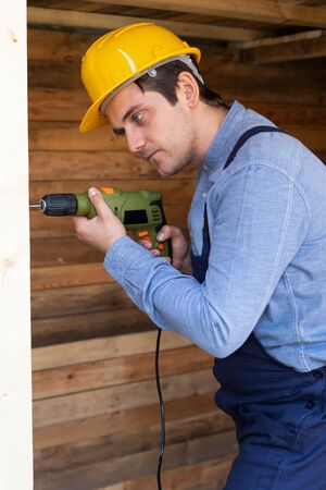 Portrait of a handsome young craftsman with yellow hard hat holding an electric drill Stock Photo