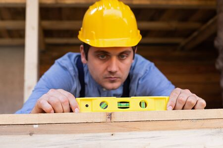 Portrait of a handsome young carpenter measuring lumber with spirit level