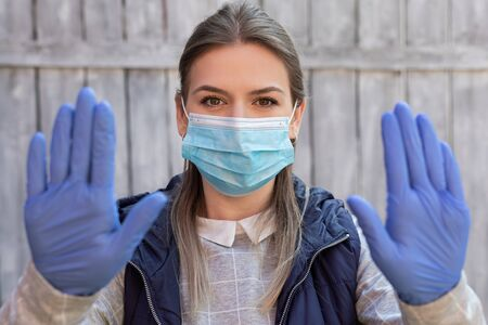 Young caucasian woman with surgical mask and gloves showing stop sign with hands