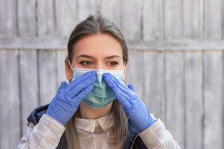 Young caucasian woman with surgical mask and gloves posing outdoor in quarantine - self isolation