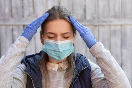 Young caucasian woman with surgical mask and gloves having coronavirus symptoms: headache, fever