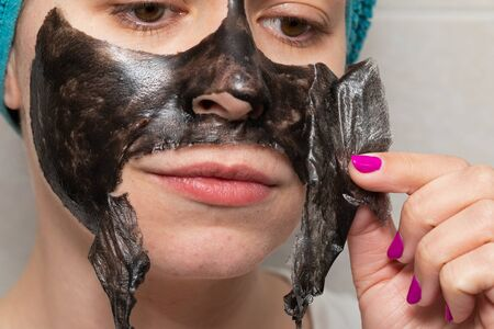 Close up picture of woman removing black charcoal peel off face mask from skin - pore cleansing treatment at home Stock Photo