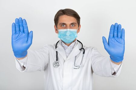Handsome young physician wearing surgical mask and gloves is showing stop sign on white background Banque d'images - 144159329