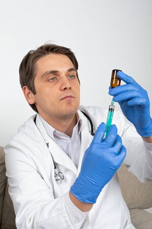 Handsome male doctor holding a bottle with liquid medication and syringe indoor