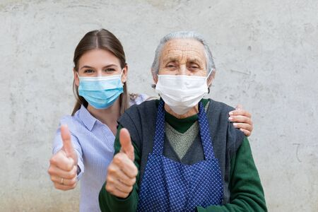 Portrait of friendly caregiver posing with elderly ill woman wearing surgical mask because of covid-19 pandemic, showing thumbs up 免版税图像