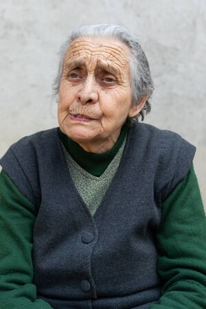 Portrait of an old widowed woman having sad face expression