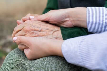 Close up picture of caregiver holding senior woman's wrinkled hands