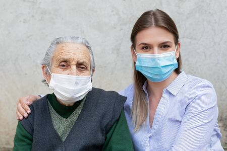 Portrait of friendly caregiver posing with elderly ill woman wearing surgical mask because of covid-19 pandemic Stock Photo