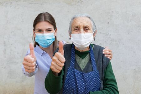 Portrait of friendly caregiver posing with elderly ill woman wearing surgical mask because of covid-19 pandemic, showing thumbs up