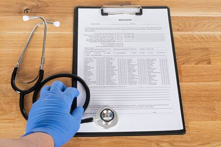 Medical record of sick patient and stethoscope on wooden table