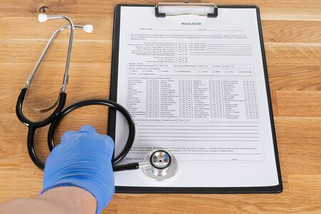 Medical record of sick patient and stethoscope on wooden table Imagens