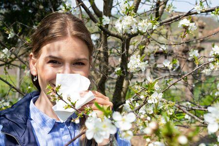 Cheerful caucasian woman having allergic reaction to springtime tree blossom Stock Photo