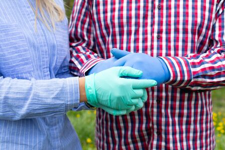 Holding hands - wearing gloves because of covid-19 pandemic - caregiver holding elderly patient's hands