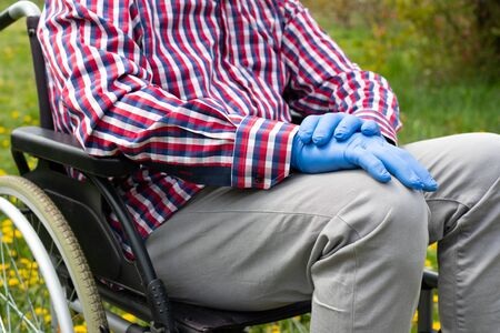 Close up picture of disabled elderly man's hand wearing gloves in time of covid-19 pandemic, sitting in a wheel chair outdoors