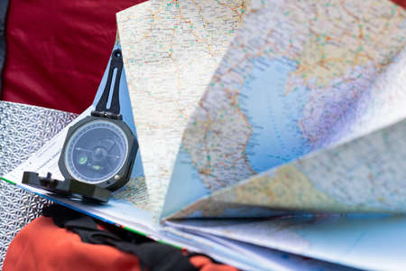 Close up picture of compass and map - preparing for camping trip in the woods 스톡 콘텐츠