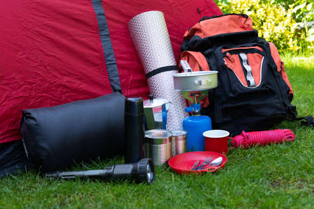 Picture of camping tools on the grass - backpack, tent, gas tank, cans, compass, etc - ready to go in the woods Banco de Imagens