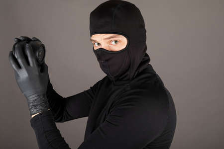 Picture of a thief dressed in black costume and wearing mask trying to turn off surveillance camera Banque d'images