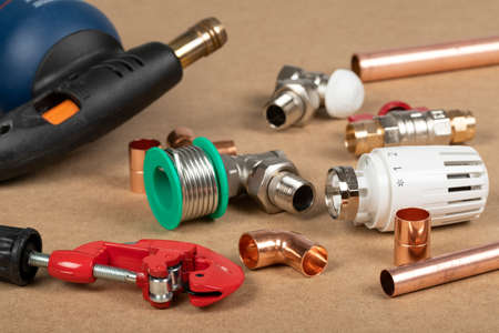 Objects of home heating system: brass valve, thermostatic valve, pipe cutter, copper plumbing parts