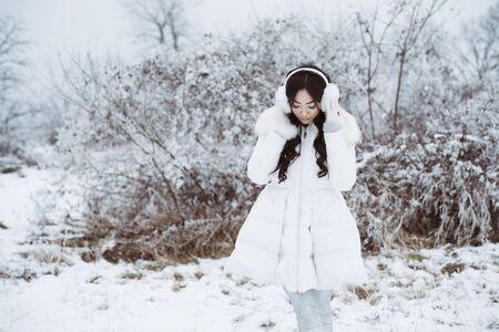 Winter portrait of young beautiful brunette woman wearing ear muffs in snow. Snowing winter beauty fashion concept.