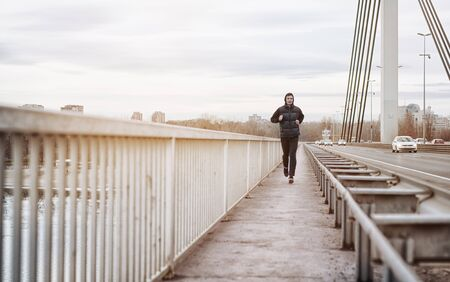 A young man running on a bridge. Guy keeping his body fit by jogging in an urban city environment on a cold winter day Stock Photo