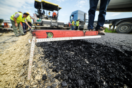 depth measurement: Heavy duty road building. Hot Asphalt being laid and measured for a quality check as a part of a on site control test. Stock Photo