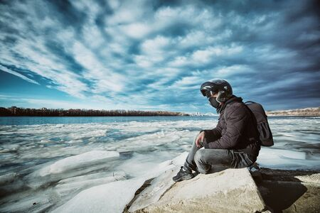 A young motorcycle enthusiast enjoying a beautiful view of a frozen river after his first winter bike ride