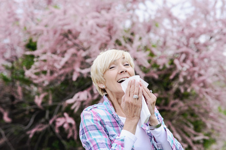 Middle aged blond woman sneezing - seasonal allergy or cold