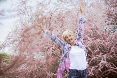 Vibrant blonde middle aged woman Happy and smiling outdoors - seasonal  Stock Photo