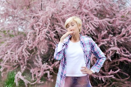 Vibrant blonde middle aged woman sneeze - spring allergies