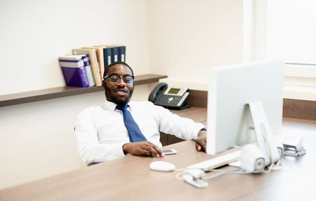 Young African American man with glasses in office