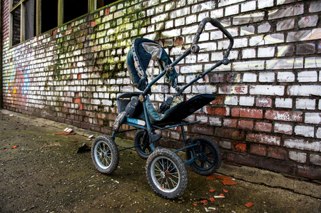 Abandoned blue stroller in front of a painted brick wall Banque d'images
