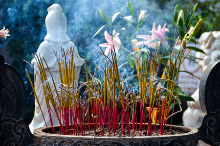 Incense holder with small statue at temple in Vietnam