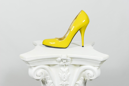 Elegant yellow female high-heeled leather shoe on greek column Banco de Imagens