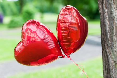 Two big red balloons with hearth shape