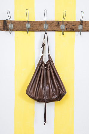 Brown purse leather on wooden wardrobe 스톡 콘텐츠