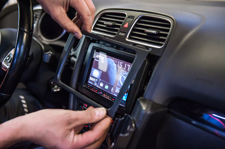 Hands mounting frame on touch display in car 스톡 콘텐츠