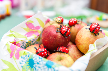 Fresh apples in a basket with chocolate ladybugs